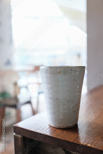 Vertical of a white clay mug on a wooden table in a cafe with blurred background - 222263230