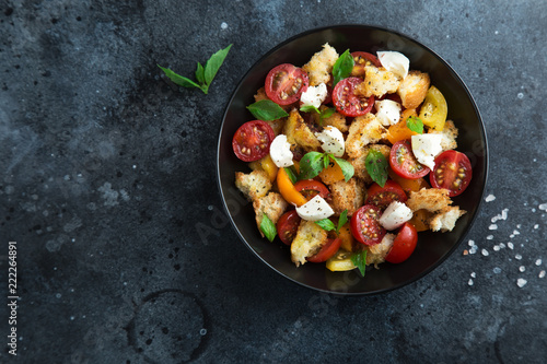 panzanella, traditional italian tomato, mozzarella and bread salad in black bowl © anna_shepulova