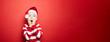 Leinwandbild Motiv Junge zu Weihnachten vor einem roten Hintergrund