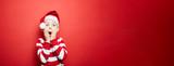 Junge zu Weihnachten vor einem roten Hintergrund