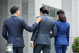 Back view of elegant trendy men and woman in suits walking together on street - 222282292