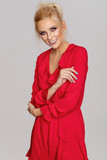 Beautiful smiling blond woman in red dress posing on gray background - 222290093