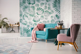 Chair and turquoise sofa in green living room interior with leaves wallpaper and table. Real photo - 222300092