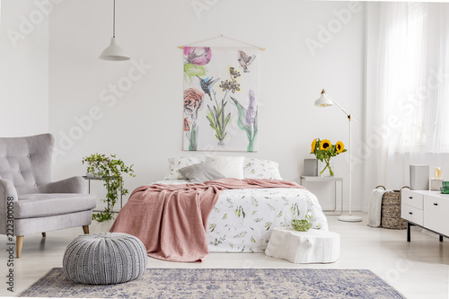 Nature lover's bright bedroom interior with a wall art of flowers and birds painted on a fabric above a bed which is dressed in green plants pattern on white linen. Real photo. - 222300058