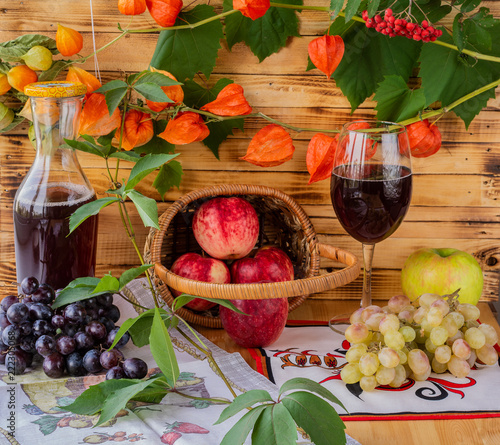 Foto Murales Still life. A rich harvest of apples and grapes on the table.