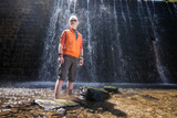 Young man with a blonde hair and beard posing for a camera in front of a waterfall