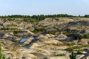 landscape - lakes at the bottom of a spent quarry of kaolin mining with beautiful slopes with traces of streams