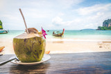 Coconut fruit drink at beautiful Tropical Beach blue ocean background with Traveler items  vacation travel accessories for holiday or long weekend a guide  choice idea for planning travel - 222328021