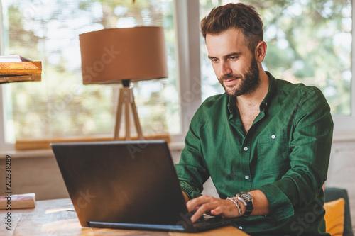 Fototapeta Young man having stressful time working on laptop
