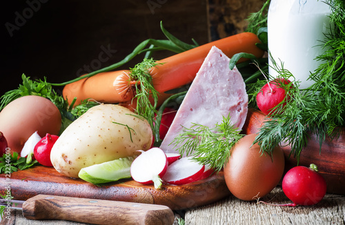 Ingredients for cold soup with vegetables, herbs and meat products, old wooden table, selective focus - 222340010