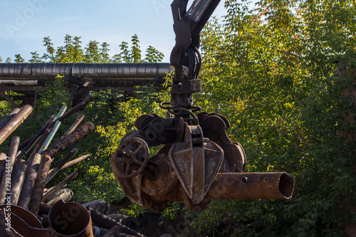 hydraulic manipulator loads old pipes | Buy Photos | AP Images