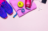 Fitness concept with Ultra violet pink female sneakers, water bottle, towel, smartphone, headphones, apple on pastel pink background flat lay top view. Sports shoes
