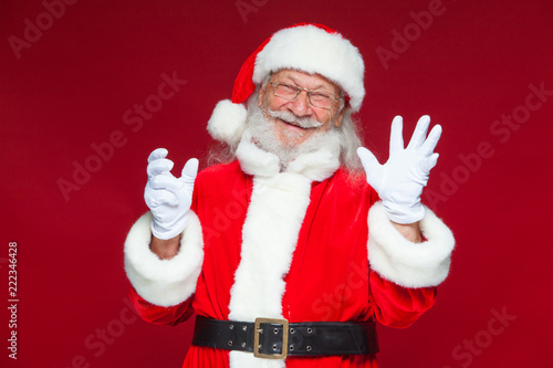 Leinwanddruck Bild Christmas. Good Santa Claus in white gloves shows faces, grimaces, shows his tongue. Not standard behavior. Isolated on red background.
