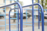 Sports bars in blue on the background of a street sports ground for training in athletics. Outdoor athletic gym equipment. Macro photo with selective focus and extremely blurred background