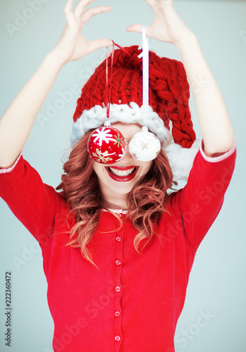 canvas print picture Beautiful happy young woman in a santa claus costume with perfect make up, red lipstick and christmas baubles, can be used as background