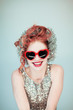 funny young lady in glitter outfit with red heart shape glasses portrait, christmas garland and red hair