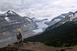 Man hiker on the steep cliff over Columbia Icefield glacier and a moraine lake. Summer storm in  Banff / Jasper National Park. Canadian Rocky Mountains.  Patterson Ridge trail. Alberta. Canada.
