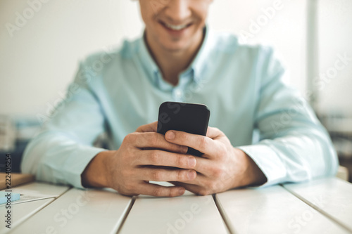 Foto Murales Digital device. Close up of a modern smartphone being held by a joyful young man