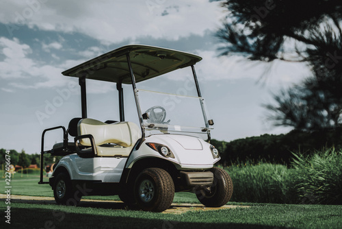 White Little Cart on Golf Field in Sunny Day. - 222406674