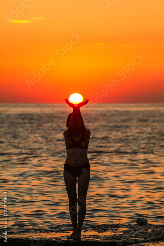Foto Murales A girl holds the sun with her hands on the sea