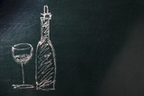 A photo of a simple drawing of a glass and a bottle of wine, made with chalk on a blackboard, with copy space - 222414099