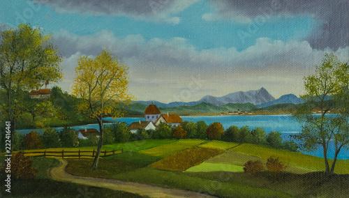 Landschaft mit Wiesen und einem kleinen Ort am See