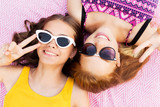 summer fashion, eyewear and people concept - smiling teenage girls in sunglasses lying on picnic blanket and showing peace hand sign - 222424822