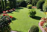 Gepflegte Gartenanlage mit Rasen und Blumen - 222429896