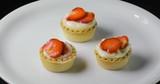 Pasticcini freschi con crema pasticciera bianca e fragole rosse. - 222431889