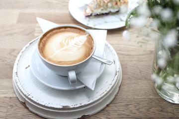 Cappuccino. Filiżanka gorącej kawy z pięknym zdobieniem na piance.