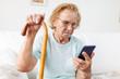 Leinwanddruck Bild - Elderly woman with glasses using a mobile phone