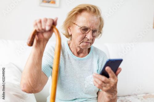 Leinwanddruck Bild Elderly woman with glasses using a mobile phone