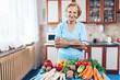 Leinwanddruck Bild - Happy senior woman with fresh crop from her garden