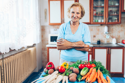Leinwanddruck Bild Happy senior woman with fresh crop from her garden