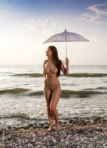 Beautiful nude woman posing with white umbrella at the beach