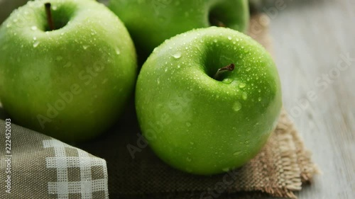 Closeup shot of whole ripe green apples with shiny drops of water composed on canvas napkin in daylight