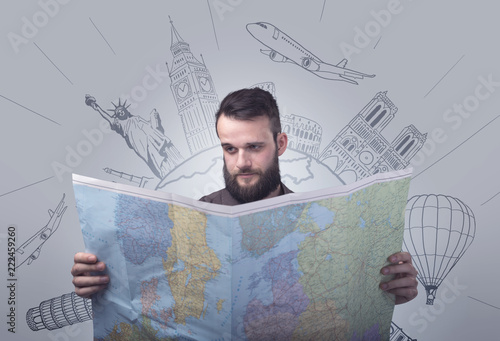 Foto Murales Handsome young man holding a map with famous sightseeing destinations above his head