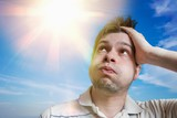 Young man is sweating. Hot weather concept. Sun in background. - 222460872