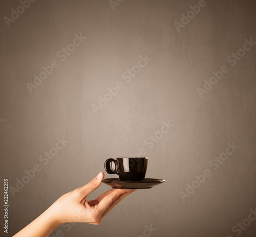 Leinwanddruck Bild Young female hand holding coffee cup with brown background