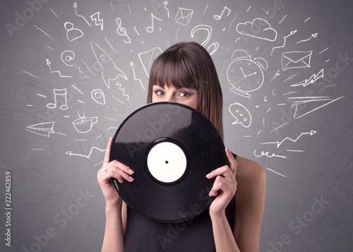 Leinwanddruck Bild Young lady holding vinyl record on a grey background with mixed scribbles behind her