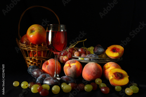 Foto Murales Fruit and a glass of red wine on a dark background