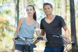 portrait of happy couple cycling outdoors - 222472635
