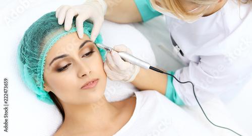 Leinwandbild Motiv Professional beautician doing eyebrow tattoo at woman face. Permanent brow makeup in beauty salon, closeup.  Cosmetology treatment