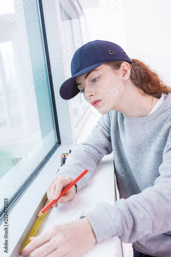 woman measuring the wall with tape measure - 222477083