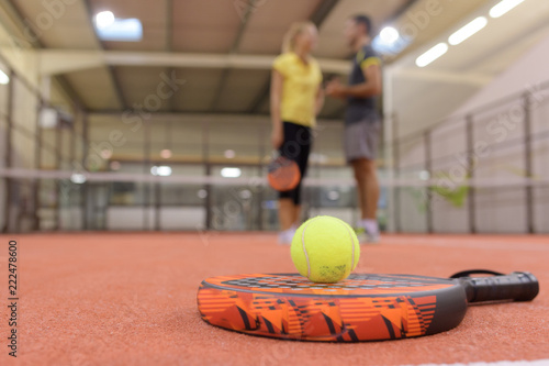 Fototapeta tennis racket and two balls near net on indoor court