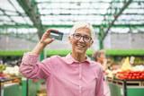 Senior woman holds credit card - 222482405
