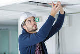 contractor unscrewing overhead ceiling panel - 222482443