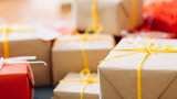 holiday traditions of present packaging and handmade wrapping. gift boxes in craft paper and tied with yellow twine - 222482825