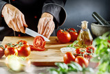 Man cutting ripe tomatoes into thin slices