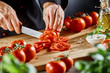 Chef slicing fresh ripe tomatoes on a board - 222484209